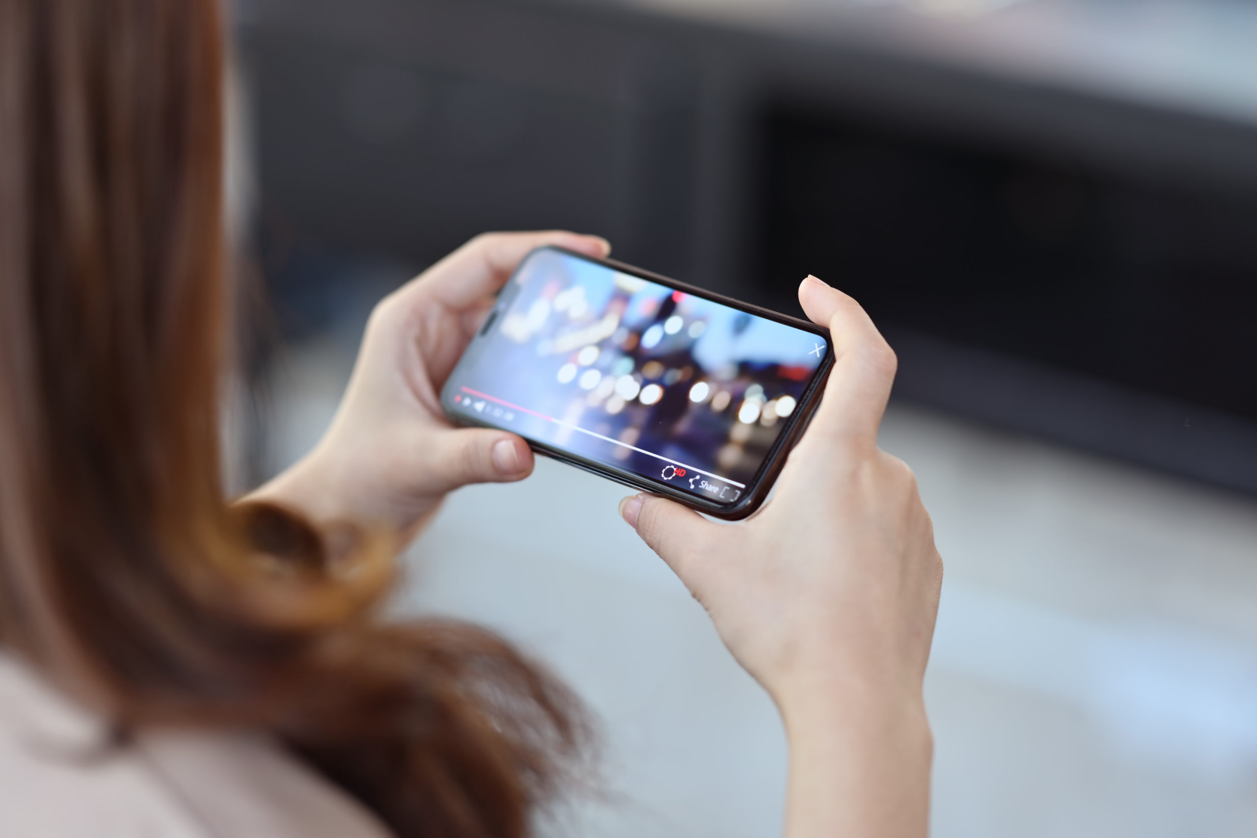 Cropped shot of female hand holding mobile phone playing video stream online